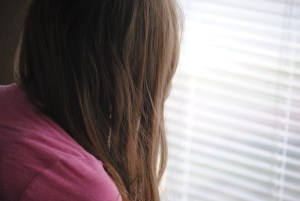 girl looking at blinds