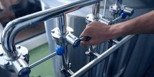 Na foto, homem ajusta equipamento para produção de cerveja; essencial contar com GLP em cervejarias