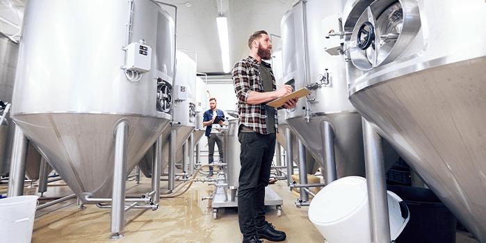 Homem circula pela estrutura da cervejaria para checar produção