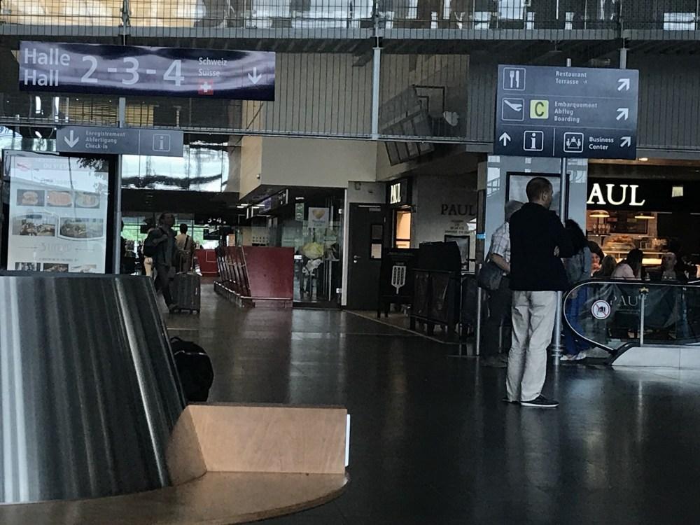Hall francês do EuroAirport e a sinalização para o lado Suíço