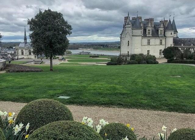 Jardins verdes e floridos mesmo no inverno delineando o castelo e a capela, com o rio ao fundo