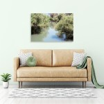 Canvas Print. Photo of the Jordan River, south of Tiberias, Israel. Green trees line the banks. The water is green and reflects the blue sky.
