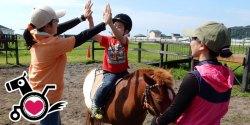 私たちが活動する北海道浦河町は全国でも有数の競走馬の産地です。浦河町では全国でも珍しく、高齢者の介護予防や障がい児の 療育といった自治体の福祉サービスとして乗馬療育が提供されています。乗馬をする年齢は2歳から90歳代まで!       幅広く町民に喜ばれる福祉サービスとして提供しています。