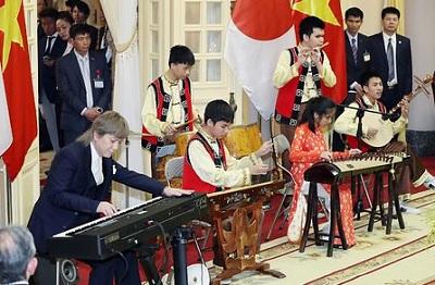 ベトナムのチャン・ダイ・クアン国家主席夫妻主催の晩さん会で、ベトナムの伝統楽器の演奏を披露する盲学校の生徒と小室哲哉さん(左)=1日午後、ハノイの国家主席府(代表撮影)