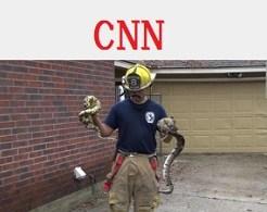 へびを捕獲させられている消防士