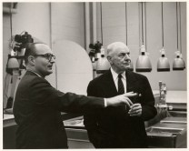 """University photographer Alfred """"Al"""" Danegger (left) showing photo processing equipment in the new Journalism Building to Dr. Thomas Symons, November 1957."""
