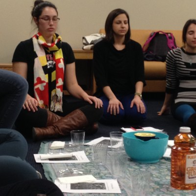 Sophomore Rebecca Hefter, Rabbi Sarah Tasman, and sophomore Shir Kantor adopt relaxed poses during guided meditation. (Photo by Jacob Schaperow)