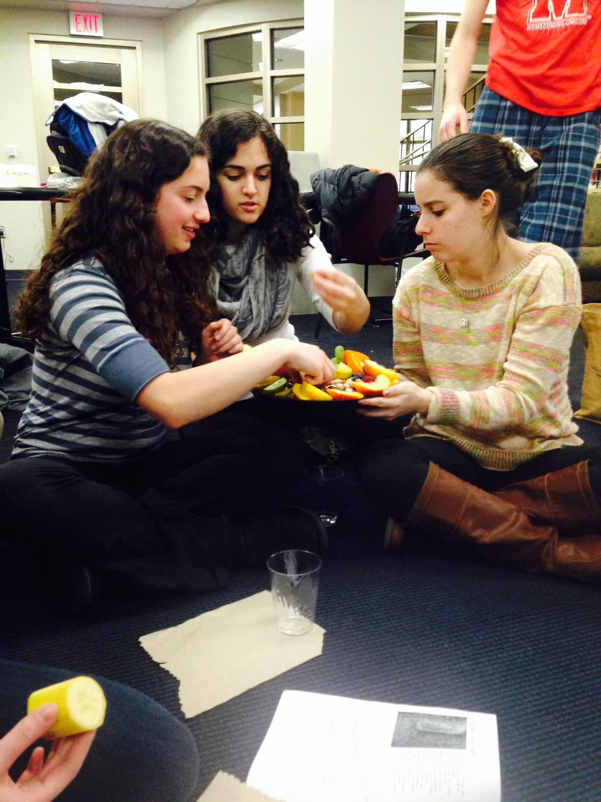 "Sophomores Melissa Robinson, Eliana Schwartz and Roxanne Jaffe divide a ""seder plate"" of fruits and nuts. (Photo courtesy of Rabbi Sarah Tasman)"
