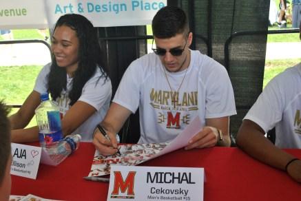 Junior Michal Cekovsky of the men's basketball team and junior Aja Ellison of the women's basketball team sign autographs for fans.