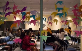 Around 60 students gather in the Cambridge Community Center to watch this year's annual drag queen prom fashion show. The room is decorated with tissue paper leaves, pink and blue streamers and came loaded with refreshments and music. (Ryan Eskalis/Bloc Reporter)