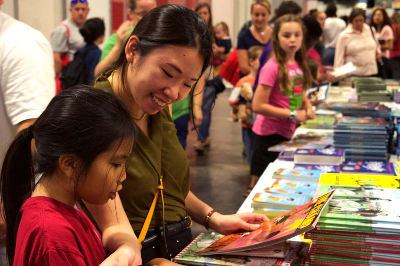 """10-year-old Bella Nguyen from Arlington, Va. reads books from the children's table with her """"bud"""" Ruth Tam, 25, a Washington, D.C. resident at the 16th Annual National Book Festival Saturday Sept. 24, 2016. (Jordan Stovka/Bloc Reporter)"""