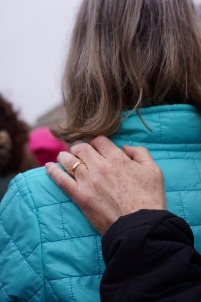 Man in the crowd places his hand on his wife's shoulder reassuringly. (Heather Kim/Bloc Photographer)