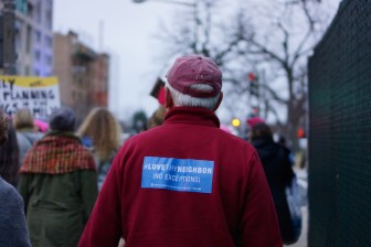 An elderly man walks proudly among the marchers with a sweater that promotes love with no exceptions. (Heather Kim/Bloc Photographer)