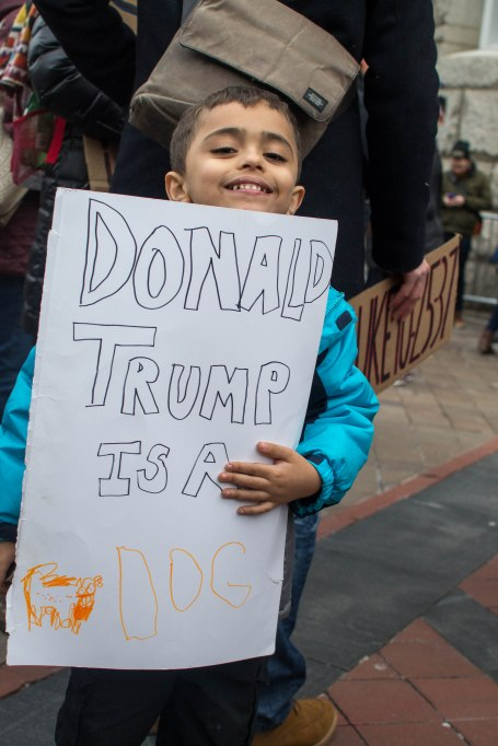 A child (whose name will not be published at the request of his mother) proudly holds a sign that he made by himself for the protest. Oddly one of the more civil signs featured all day. (Joe Duffy/Bloc Photographer)