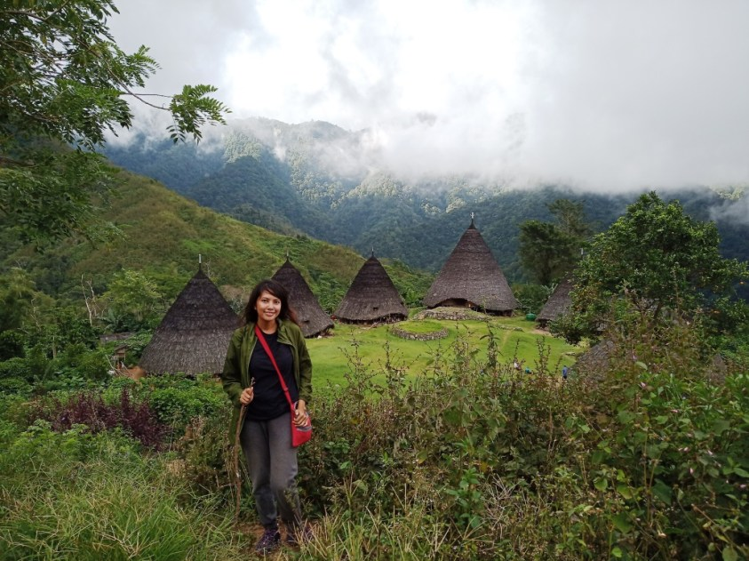 Me with Wae Rebo conical houses in the backgrounf