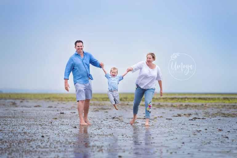 Happy family on the beach, photographed near Horsham by Umoya Photography