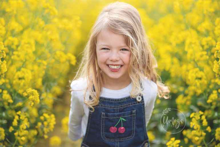 Girl smiling in yellow fields during a family photoshoot in Horsham