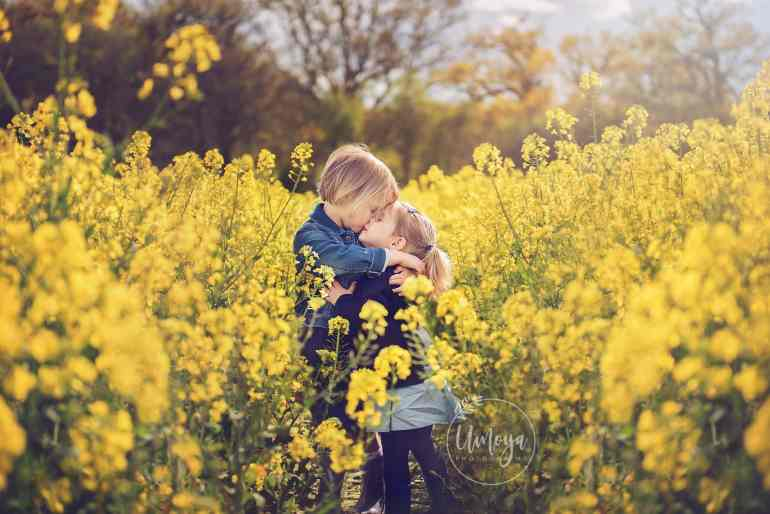 Sisters hugging in yellow flowers