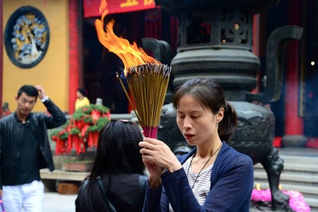 Fiel em oração no Templo Budista.