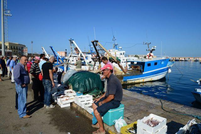 Pescadores vendem o peixe do dia no cais do porto.