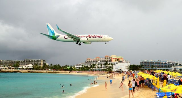O avião passa sobre as cabeças dos banhistas.