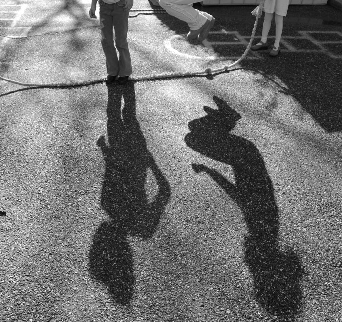 A photo of upside-down shadows of children jumping rope, black-and-white by aptmetaphor on Flickr