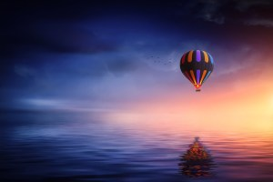 A picture featuring a rainbow hot air balloon floating over water at sunset by Bess-Hamiti on Pixabay