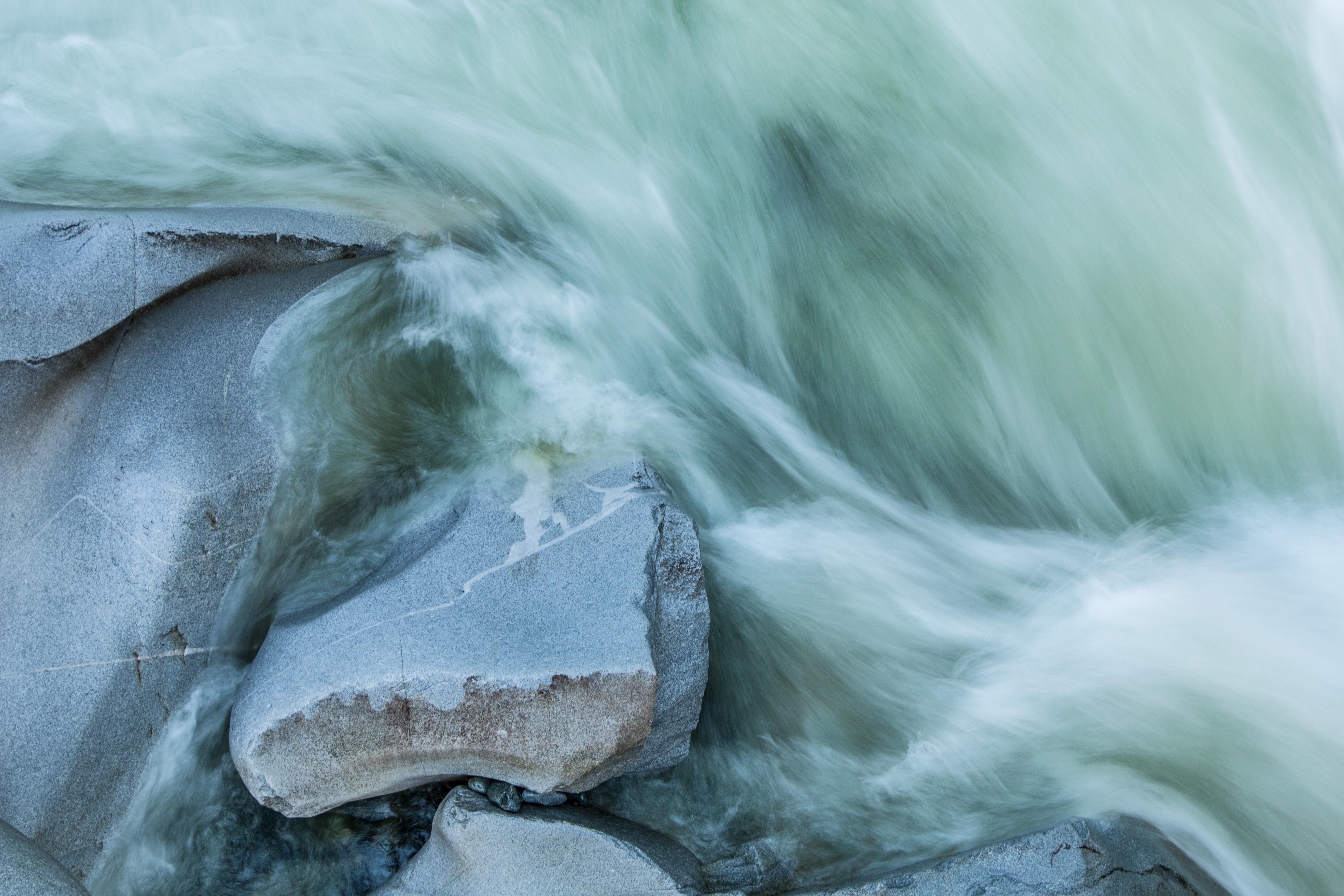 Swirling sea waves foaming against smooth rocks