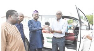 Director DUFARMS, Mr Joseph Olabasola receiving the keys of the SUV from the Vice Chancellor