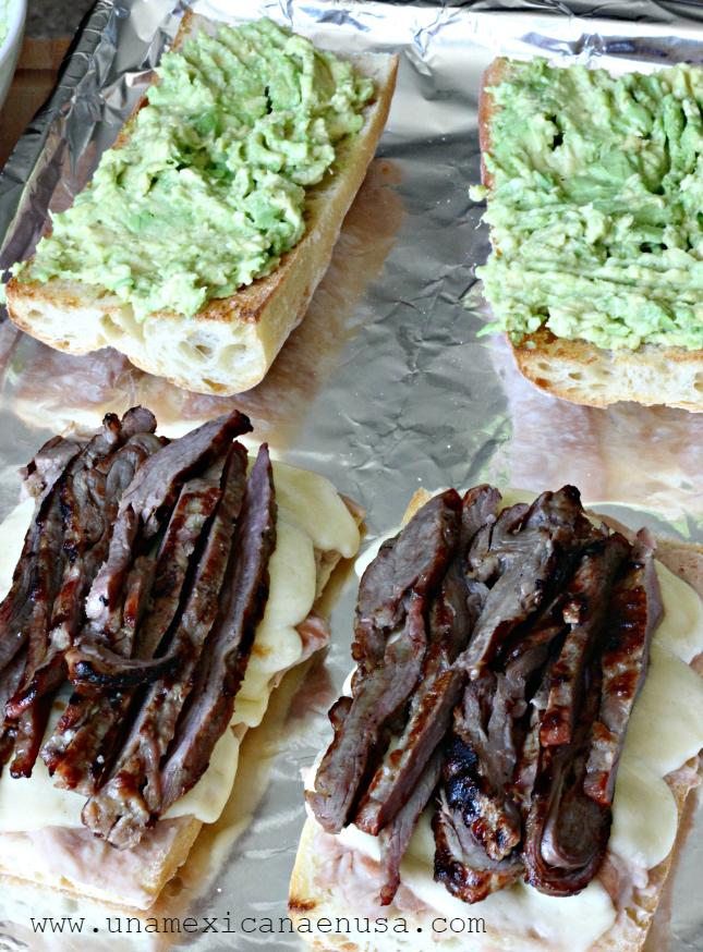 Panes partidos a la mitad, dos de ellos con aguacate machacado y dos con frijoles refritos, queso Oaxaca derretido y tiras de carne asada.