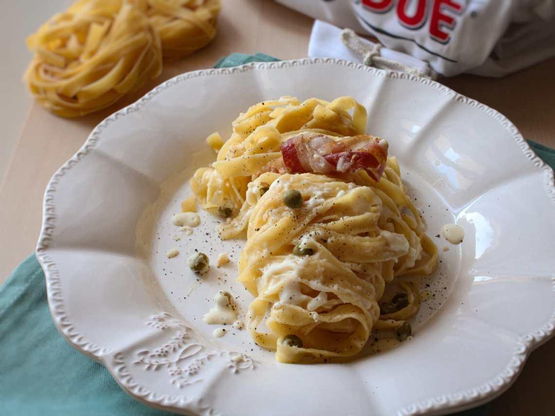 piatto di tagliatelle con crema di formaggio piselli e pancetta