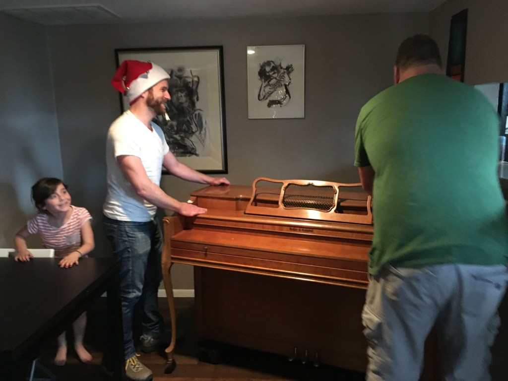 Dave Madden giving a piano to a little girl who wanted a piano for Christmas