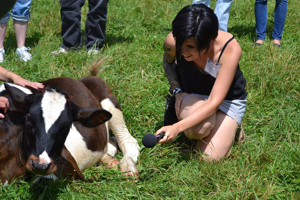 Jasmin Singer with a calf at Farm Sanctuary, Watkins Glen, NY. Photo credit: Cameron Icard.