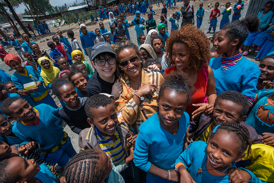 L-R: A Well-Fed World Founder Dawn Moncrief, IFA Founder Seble Nebiyeloul, and IFA School Health and Nutrition Program Coordinator Nardos Alemayehv, surrounded by children at a school outside Addis Ababa where IFA plant-based lunch programs are delivered.