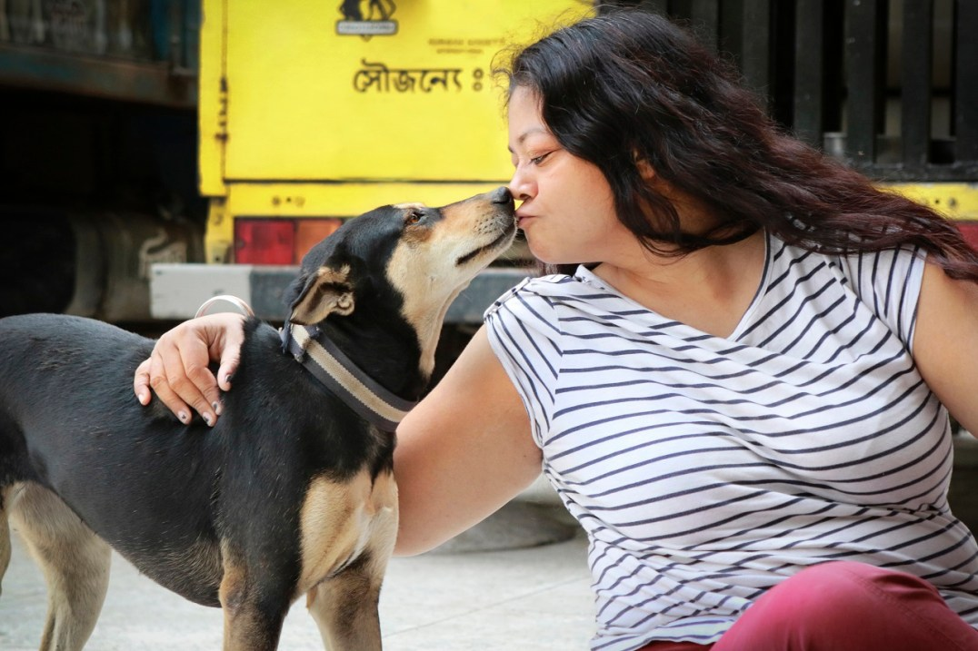 Rubaiya Ahmad with one of the free-roaming dogs that Obhoyaronno treats