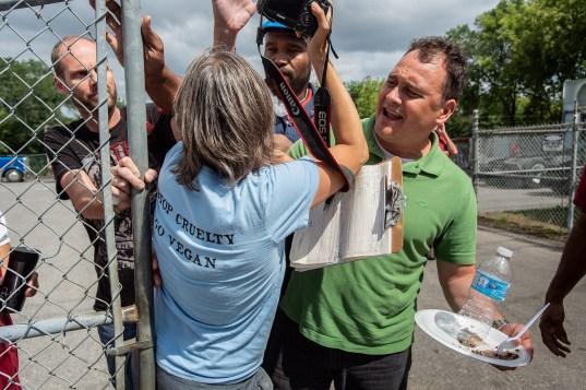 Slaughterhouse employees force Anita Krajnc away from the gates. Canada, 2015.