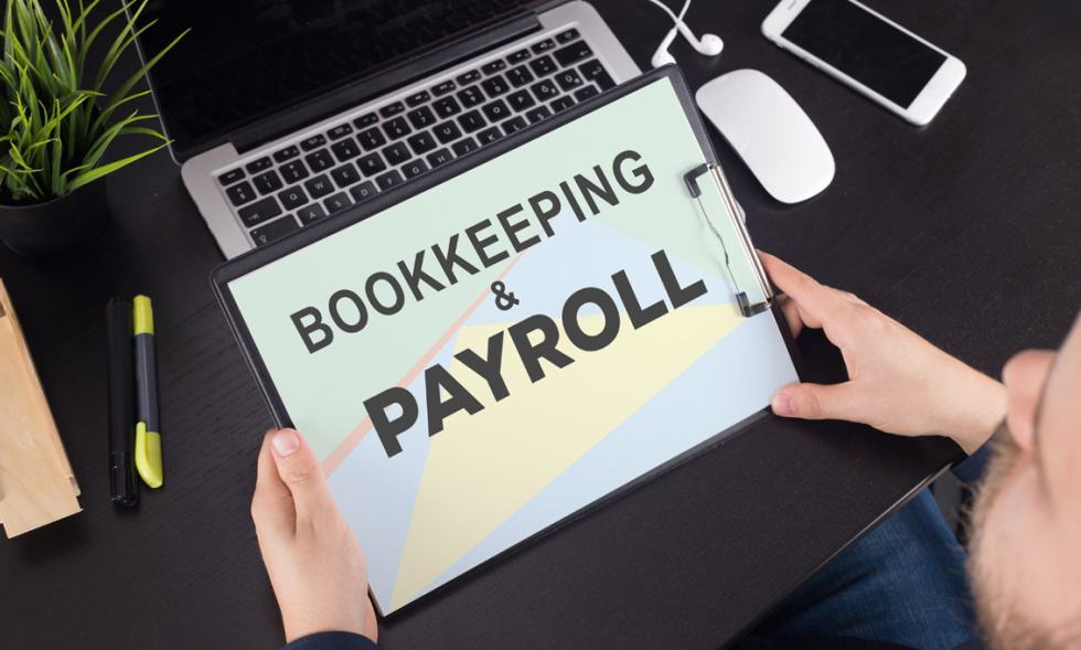 Business Page - the words bookkeeping and payroll on a clipboard with a laptop, cellphone, mouse and earphones in the background