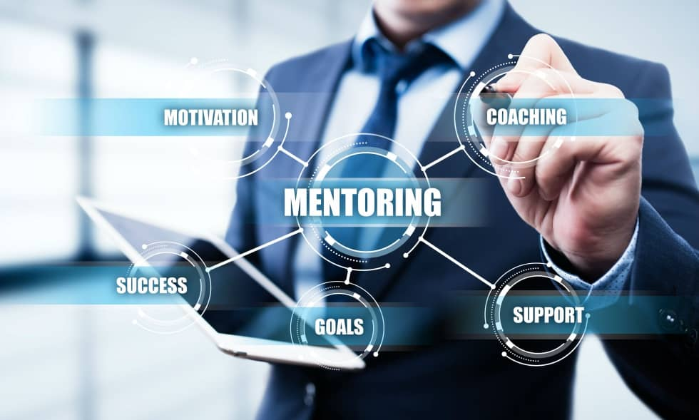 a man in a suit in the background with a foreground interface that lists a mindmap linking the words Motivation, Coaching, Success, Goals and Support linked to Mentoring in the center.