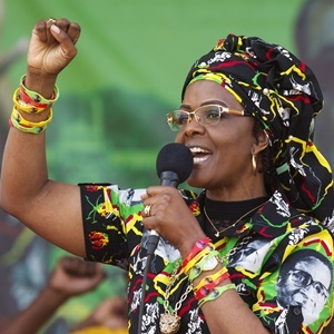 FILE -- In this July 29, 2017 file photo Zimbabwe's First Lady Grace Mugabe greets supporters at a rally in Zimbabwe. South Africa's police minister says the wife of Zimbabwe's president, background image, has handed herself over to police after being accused of assaulting a young woman Sunday night. (AP Photo/Tsvangirayi Mukwazhi, File)
