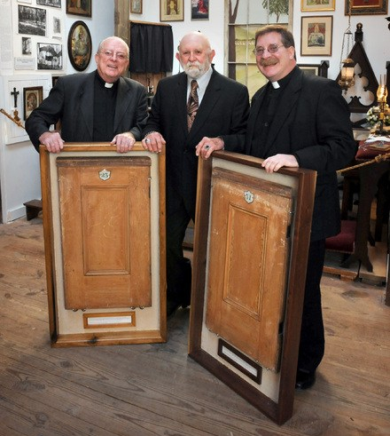 From left, Monsignor Richard Youtz, Ken Hoak and the Rev. Leo Goodman pose with pew doors from the Immaculate Conception of St. Mary's Catholic Church.