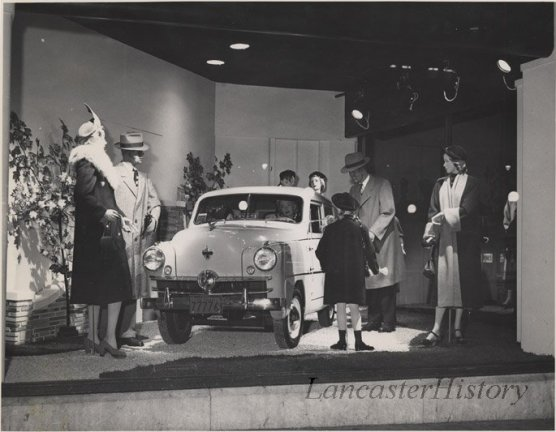 Store window display at Watt and Shand. Shows men's, women's and children's clothing and an automobile around 1950.