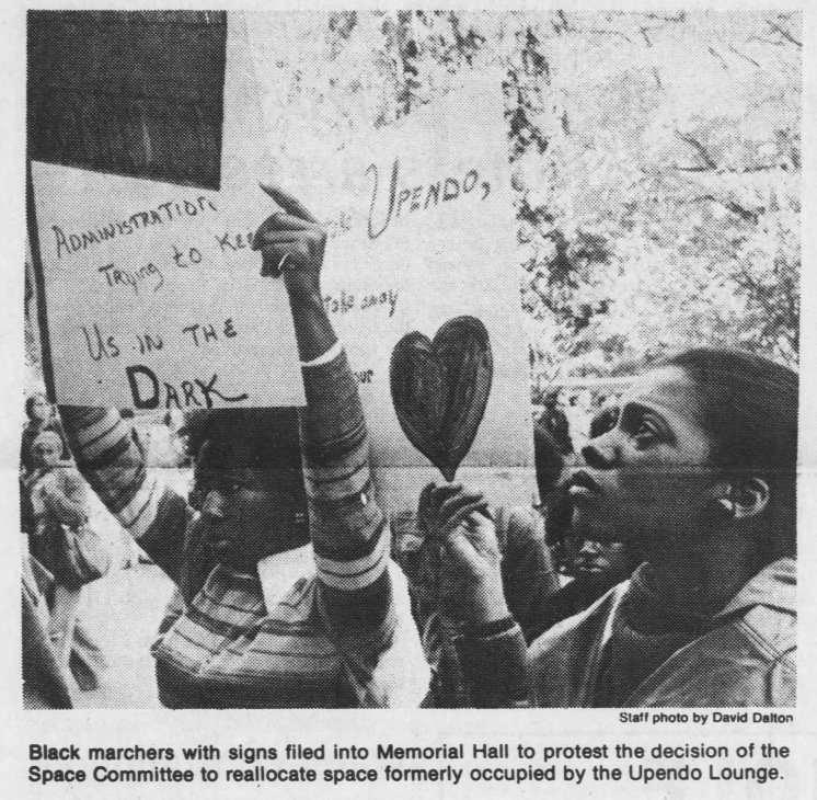 """Black marchers with signs filed into Memorial Hall to protest the decision of the Space Committee to reallocate space formerly occupied by Upendo Lounge."" Photo by David Dalton in The Daily Tar Heel, 13 October 1976, Page 1."