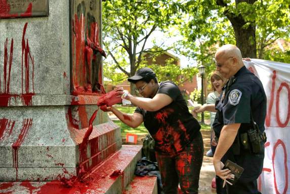 Maya Little, Graduate student in History Department, pouring a mixture of paint and blood onto the Confederate Monument, Photo by Adam Lau in The Durham News Herald, 30 April 2018.