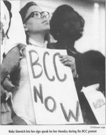 """Ruby Sinreich protests during University Day proceedings, 1992. Photo by Jayson Singe in Griffin, Anna, """"BCC Protest Interrupts University Day event,""""The Daily Tar Heel, 13 October 1992, Page 1."""