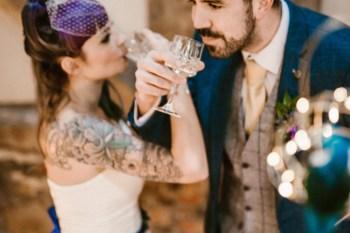 Peacock barns - alternative unconventional wedding photoshoot - rustic decadent - couple drinking fizz