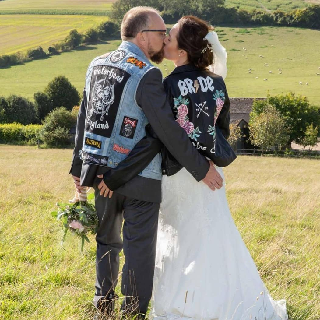 alternative wedding couple with hand painted jackets - bride jacket with pink roses - groom denim jacket motorhead - outdoor wedding - field view - alternative wedding wear ideas