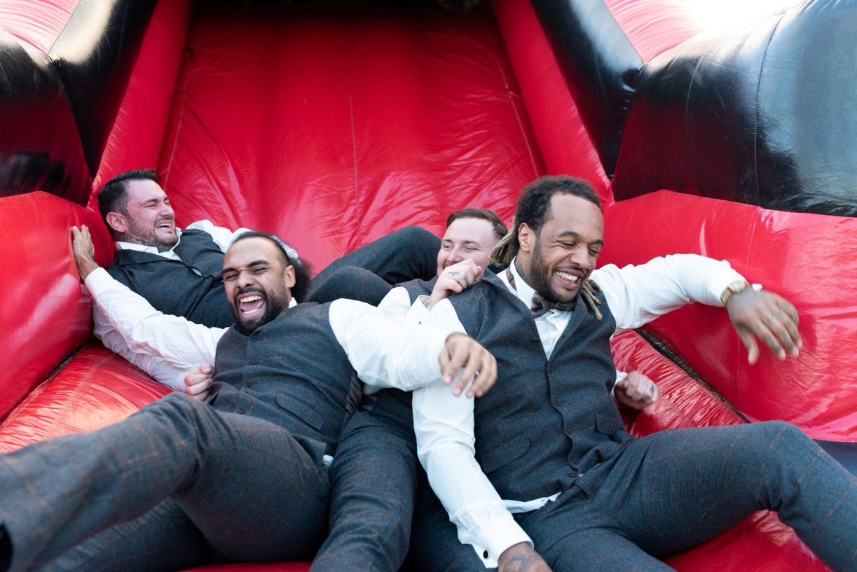 Getting Married Abroad- Grooms Perspective- Wedding Planning for Men- Unconventional Wedding- Pudding And Plum Photography- Photography- Groomsmen on bouncy castle