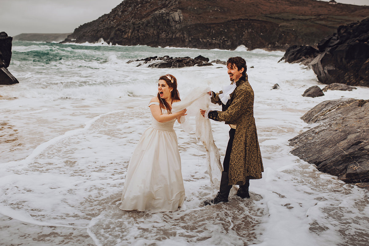 Bride and groom in the sea - outtake from couples photoshoot from labyrinth movie themed wedding day in cornwall