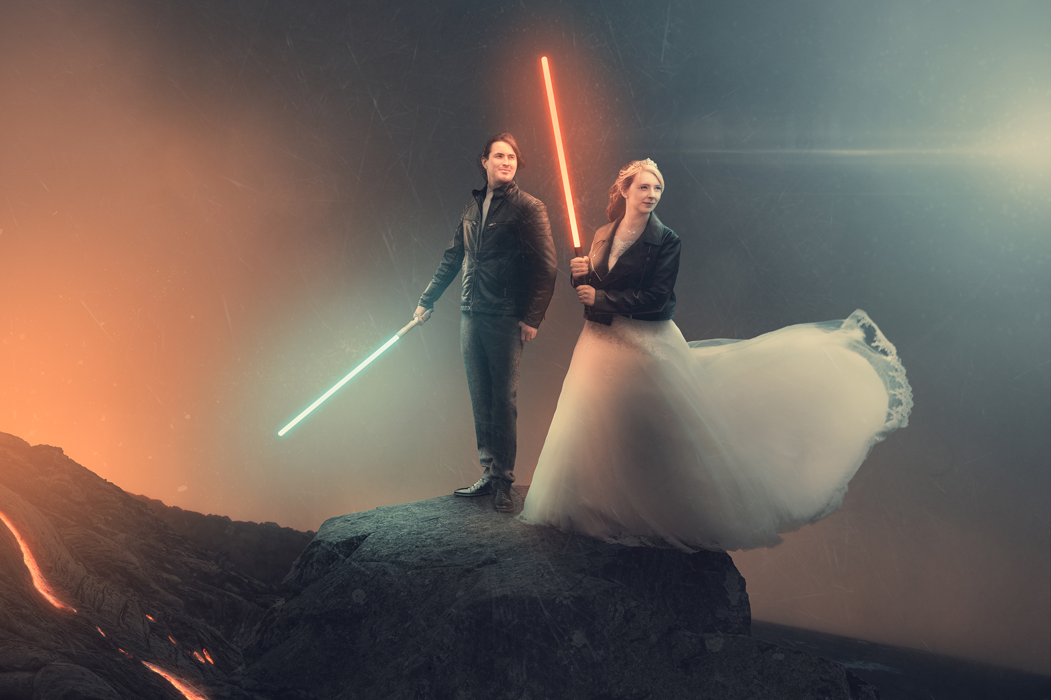Lightsaber wedding photo - bride & groom holding red and blue light sabers on top of a mountain with lava - sci fi wedding photo - creative wedding ideas - star wars wedding photo