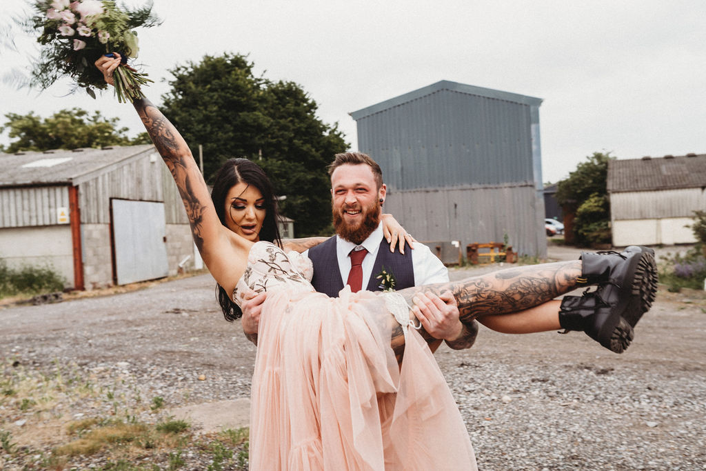 groom carrying bride - bride in dr martens - alternative farm wedding, edgy wedding, tattooed wedding, alternative wedding -